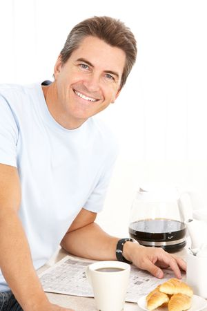 Adult smiling man having lunch in  kitchen  photo
