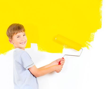 smiling boy painting interior wall of home.   photo