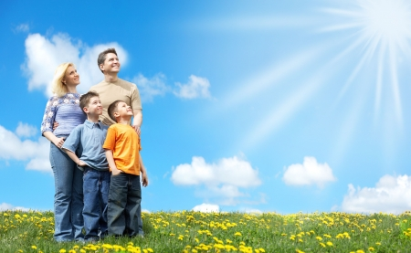Family under blue sky. Father, mother and sons in the park