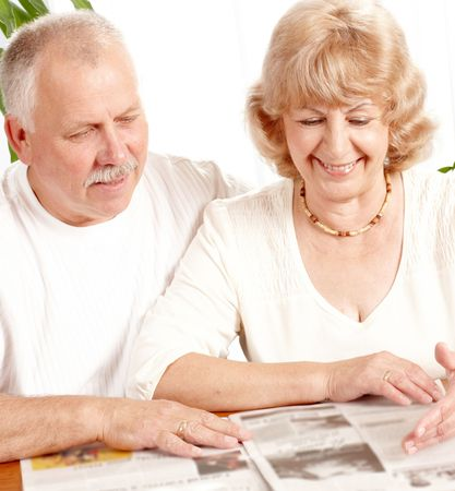 senior couple reading a magazine  at home photo