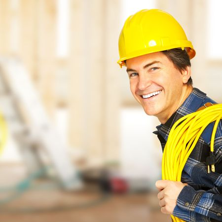 Smiling handsome builder in yellow uniform.   photo