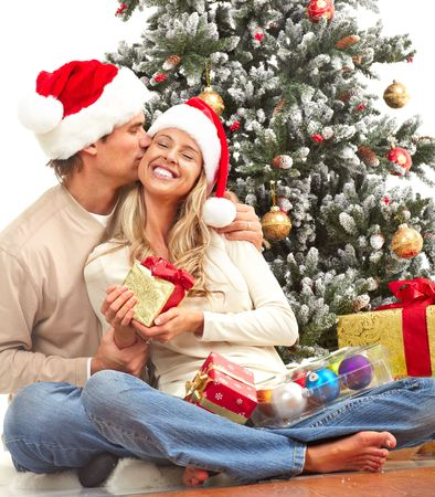 Young happy couple near  a Christmas tree. Over white background