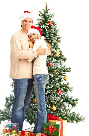 Young happy couple near  a Christmas tree. Over white background Stock Photo - 5987587