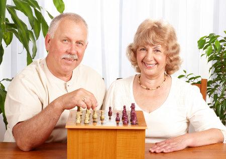jugando ajedrez: Senior par jugar al ajedrez en casa Foto de archivo