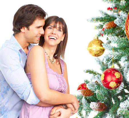 Young happy couple near  a Christmas tree. Isolated over white background  Stock Photo