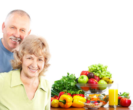 healthy seniors: smiling seniors couple with fruits and vegetables. Over white background