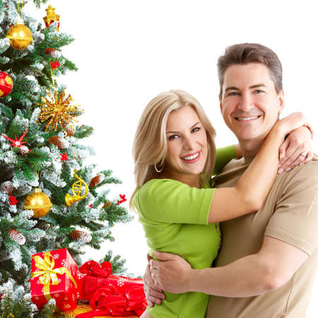 winter woman: Young happy couple near  a Christmas tree. Isolated over white background  Stock Photo