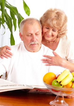 senior couple reading a magazine  at home  photo