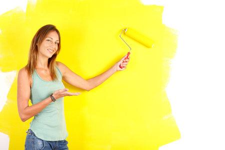 Renovatie. Lachende mooie vrouw schilderij interieur wand van huis.  Stockfoto