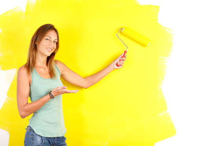 Renovation. Smiling beautiful woman painting interior wall of home.   photo