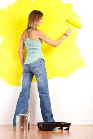 paints: Renovation. Smiling beautiful woman painting interior wall of home.   Stock Photo