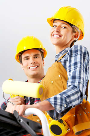 home decorating: Young smiling builder people in yellow uniform