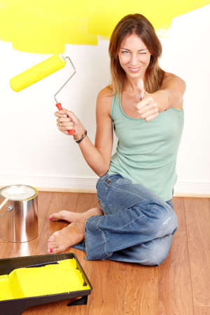 Renovation. Smiling beautiful woman painting interior wall of home. Stock Photo - 6069660