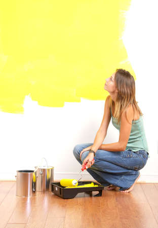 Renovation. Smiling beautiful woman painting interior wall of home.   Stock Photo