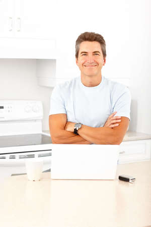 Young smiling man working with laptop in  kitchen