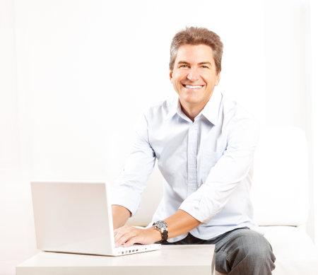 Gelukkig lachende man met laptop thuis  Stockfoto