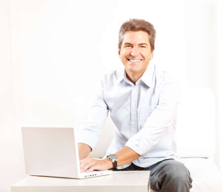 white sofa: Happy smiling man with laptop at home