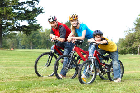 Happy family. Father, mother and son riding  in the park Stock Photo - 6111529