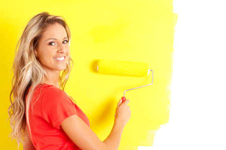 smiling beautiful woman painting interior wall of home.   photo