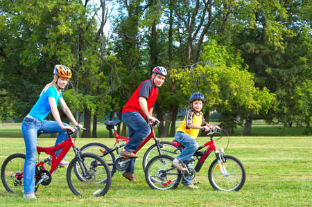 Happy family. Father, mother and son riding  in the park Imagens