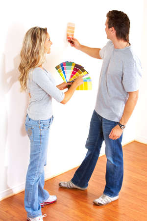 decorando: pareja sonriente elegir el color de la pared interior de la casa.