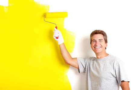 wall decor: Smiling handsome man painting interior wall of home.