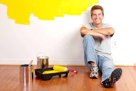 Sonriente hombre guapo pintura la pared interior de la casa.  Foto de archivo