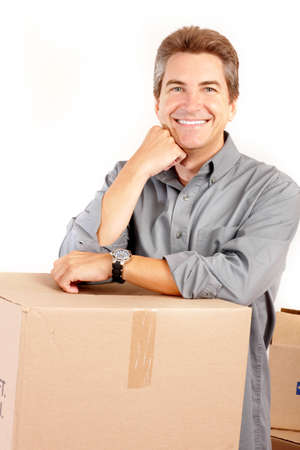 settler: Handsome man  with boxes  in the new apartment after moving