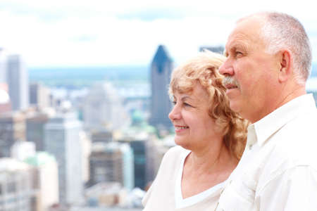 Smiling happy elderly senior  couple in the city