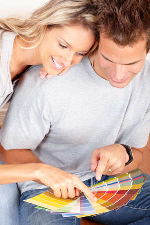 paints: smiling couple choosing color for the  interior wall of home.