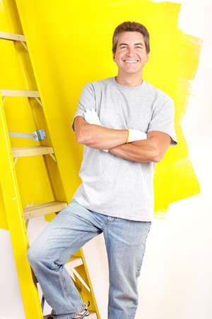 wall decor: Smiling handsome man painting interior wall of home.   Stock Photo