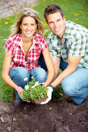 Young love couple smiling planting flowers  photo