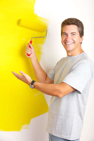man painting: Smiling handsome man painting interior wall of home.   Stock Photo