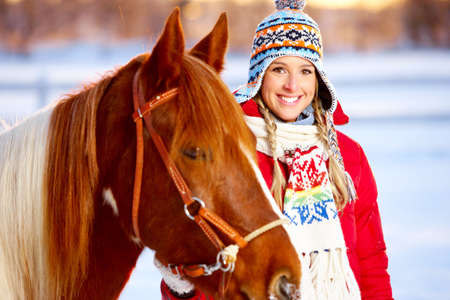 winter: Young  happy smiling woman with horse. Winter sport