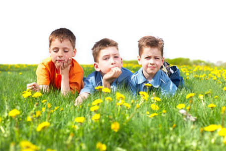 Funny smiling boys  on the green grass in the park photo