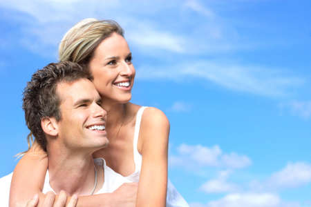 Young love couple smiling under blue sky Stock Photo - 6172309