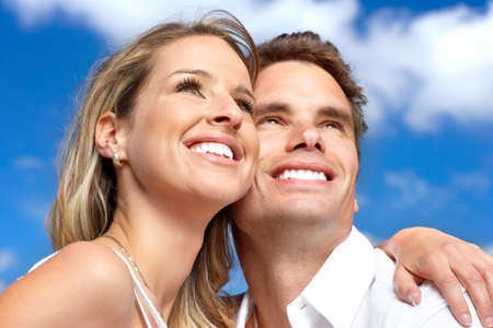 dental insurance: Young love couple smiling under blue sky  Stock Photo