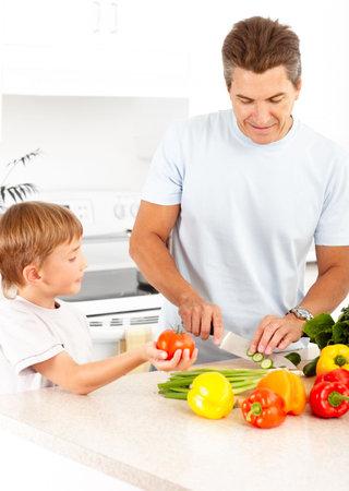 niños cocinando: Familia feliz. Padre e hijo que se cocina en la cocina