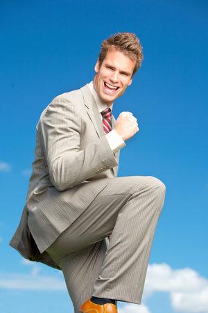 Happy successful  businessman  under blue sky.   photo