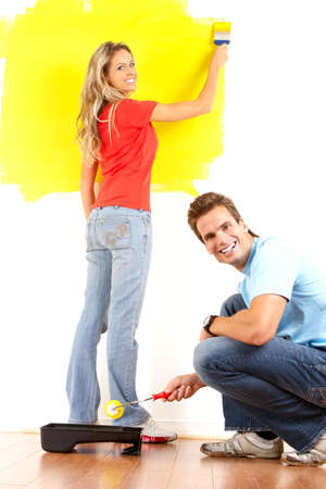 smiling couple painting interior wall of home.   Banco de Imagens