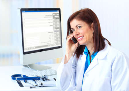 practitioner: Smiling medical doctor woman with computer and telephone.   Stock Photo