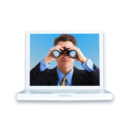 white laptop and businessman with binoculars. Over white  photo