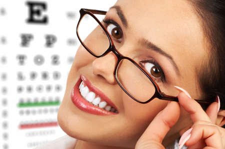 exams: Beautiful young smiling woman with eyeglasses and eyechart