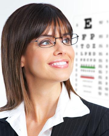 eyeglasses: Beautiful young smiling woman with eyeglasses and eyechart