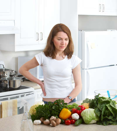 Young smiling woman  cooking at the kitchen  photo