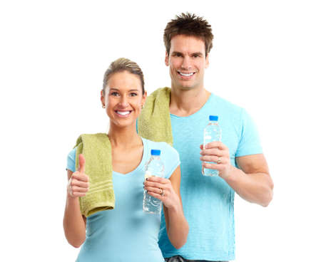 man drinking water: Fitness. Smiling young  strong man and woman. Isolated over white background  Stock Photo