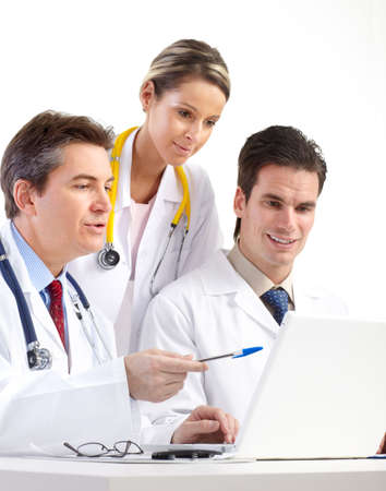 Smiling medical doctors with stethoscopes and laptop. Isolated over white background  photo