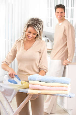 laundry room: Happy young beautiful woman ironing clothes
