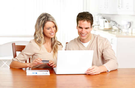 Young happy couple with laptop at home