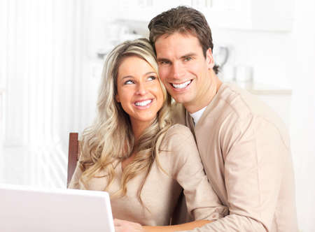 settler: Young happy couple in love with laptop at home  Stock Photo